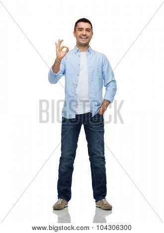 happiness, gesture and people concept - smiling man showing ok hand sign