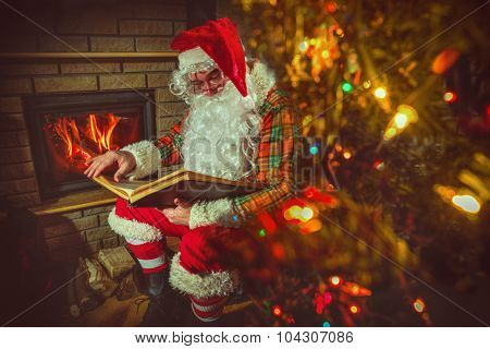 Santa Claus sitting at home near Christmas tree and  resting by his fireplace