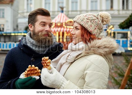 holidays, winter, christmas and people concept - happy couple in warm clothes walking in old town