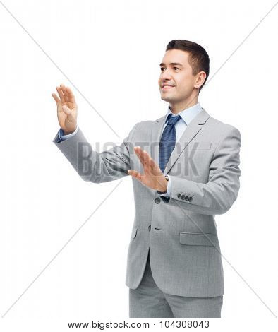 business, people and office concept - happy smiling businessman in suit touching something imaginary