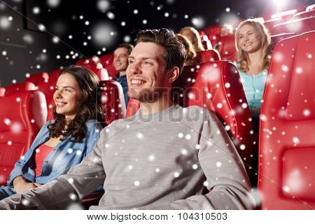 cinema, entertainment and people concept - happy friends watching movie in theater with snowflakes