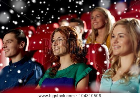 cinema, entertainment and people concept - happy woman with friends watching movie in theater over snowflakes