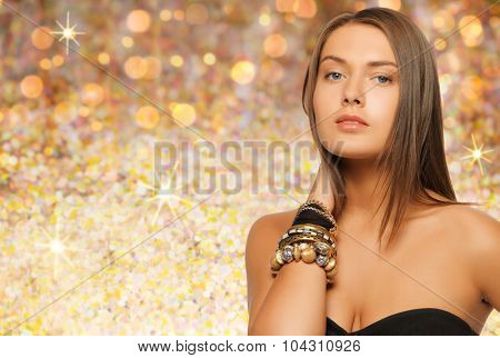 beauty, luxury, people, holidays and jewelry concept - beautiful woman with bracelets over golden lights background