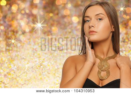 beauty, luxury, people, holidays and jewelry concept - beautiful woman wearing golden necklace over lights background