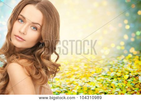 people, beauty, hair and skin care concept - beautiful woman with curly hairstyle over yellow holidays lights background