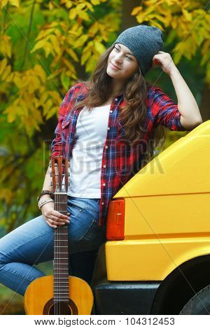 Romantic Travelling Young Girl Guitarist Player With Her Guitar At Yellow Microbus And Autumn Fallen