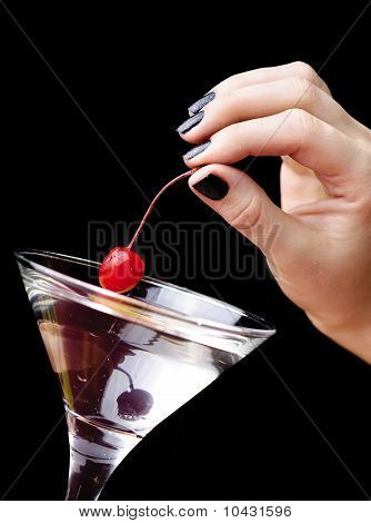 The Hand Putting The Red Cherry To The Martini Glass