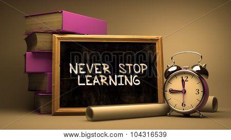 Never Stop Learning Handwritten by white Chalk on a Blackboard.