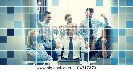 business, people, technology, gesture and teamwork concept - smiling business team raising hands and celebrating victory in office over blue squared grid background
