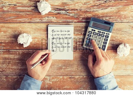 business, education, people and technology concept - close up of male hands with calculator, cramped paper wads and notebook solving mathematical task or equation