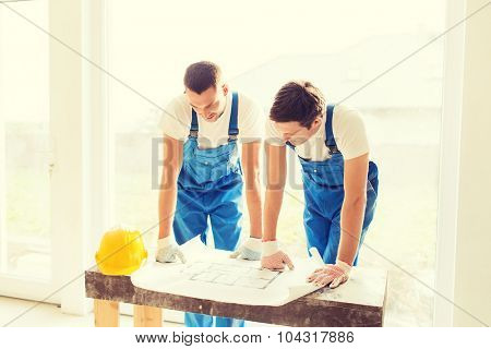 business, building, teamwork and people concept - group of smiling builders with blueprint and hardhat indoors