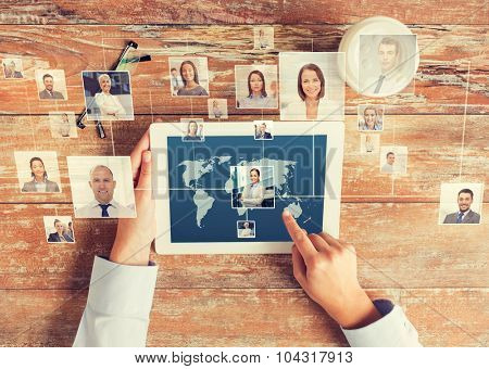 business, people, international communication, headhunting and technology concept - close up of hands pointing finger to tablet pc computer screen with world map and internet contacts network on table