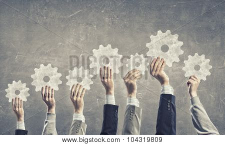 Group of business people with raised hands holding cogwheels