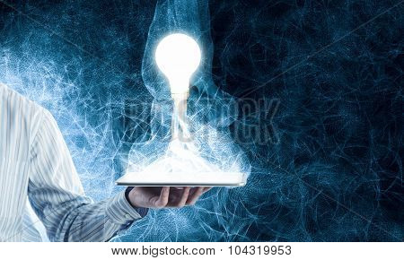 Human hands holding tablet pc with light bulb on it