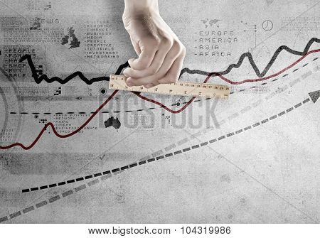 Close up of hand measuring growing graph with ruler