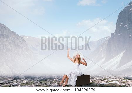 Woman in white long dress and hat sitting on her luggage