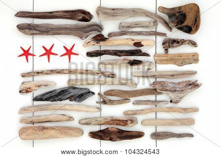 Driftwood abstract with red starfish sea shells on a white wooden background.