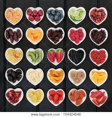 Superfood fruit selection in heart shaped bowls over wooden black background.