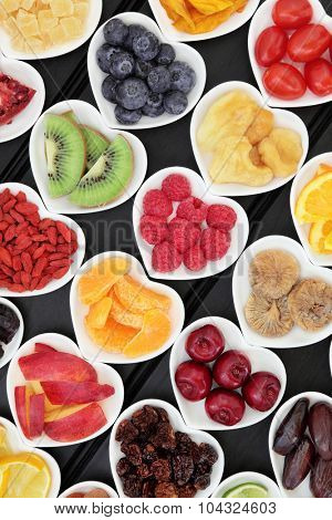 Fresh and dried mixed fruit superfood selection in heart shaped bowls over wooden black background.