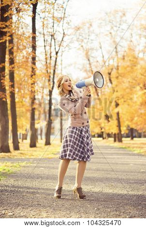 Attractive young woman yelling with loudspeaker in the autumn park.
