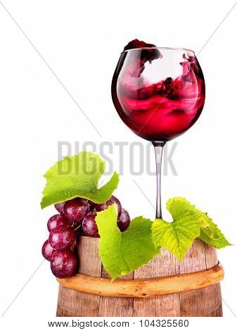 Glass of red wine with grape on a wooden barrel