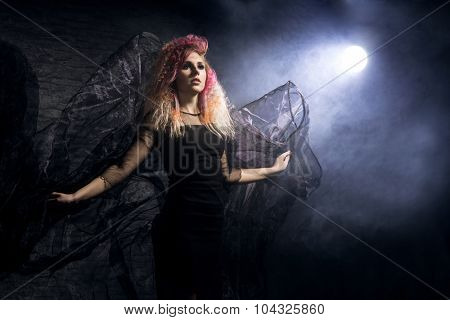 Witch in a blowing textile over the Halloween  background.