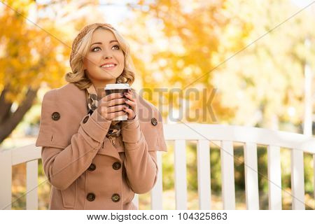 Attractive girl getting refreshment with coffee sitting on the bench in the park in autumn.