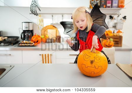 Halloween Dressed Girl Creating Pumpkin Jack-o-lantern