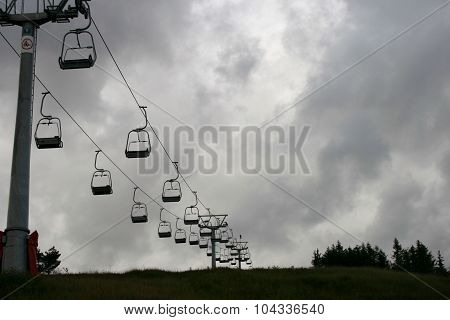 Ski Chair Lift Going Up A Mountain On An Overcast Day