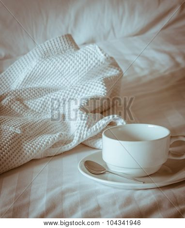 Coffee Cup With White Bathrobe On The Bed