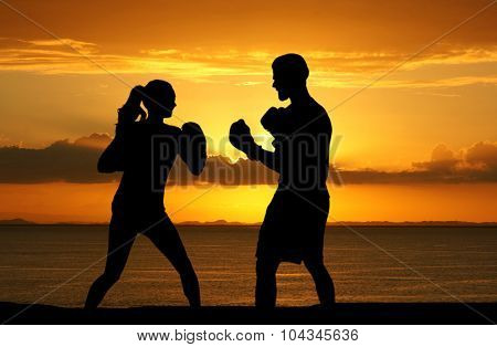 A couple boxing together while on the beach