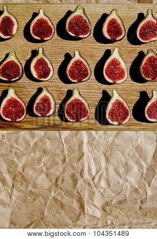 Group Of Half Splitted Figs On Wooden Plate On Craft Paper