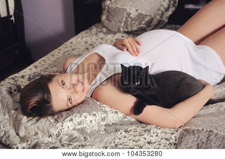 Cute smiling pregnant woman lying in bed with black cat.
