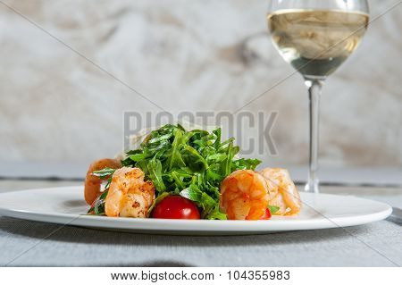 Delicious salad with shrimps, arugula, cherry tomatoes and Parmesan cheese, seasoned with balsamic s