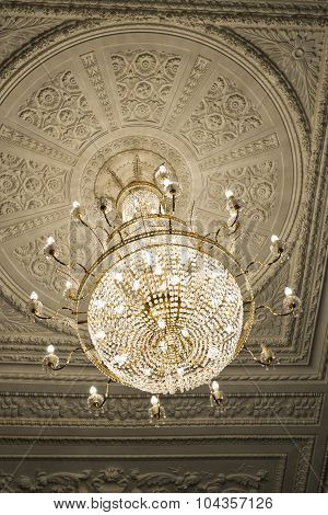 Crystal chandelier, hanging beneath a white ceiling with decorative moldings