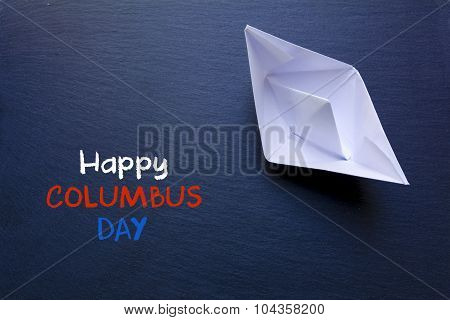 Paper boat on a chalkboard and text Happy Columbus Day