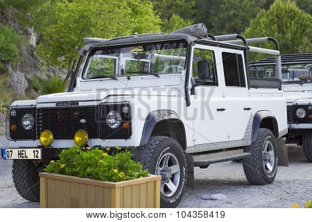 Four-wheel-drive land Rover parked at the side of the road. White SUV with the roof open. Alanya, Tu