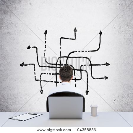 Rear View Of A Sitting Person At The Working Desk Who Is Looking At The Drawn Arrows On The Wall. A
