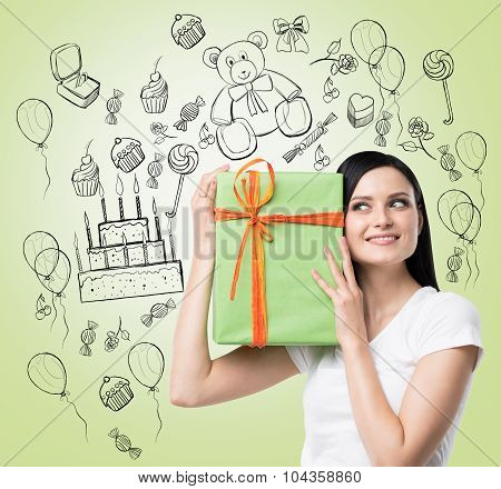 A Brunette Holds A Green Gift Box. Birthday Celebration Sketch Is Drawn On The Light Green Backgroun