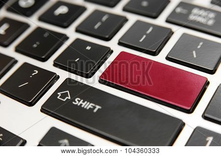 Laptop computer keyboard close up with red enter key