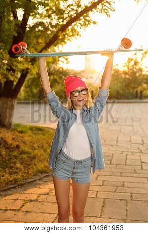 Overjoyed girl holding skateboard
