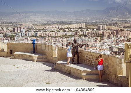 young girls are photographed on the background of the fortress of Santa Barbara, Alicante, Spain
