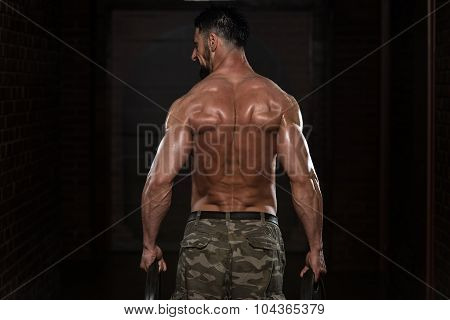 Bodybuilder Exercising Trapezius With Weights