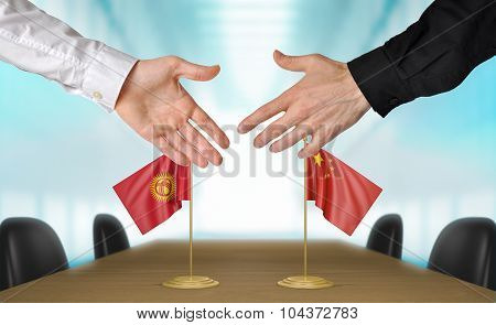 Kyrgyzstan and China diplomats agreeing on a deal
