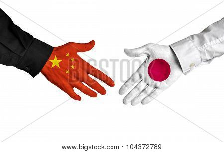 China and Japan leaders shaking hands on a deal agreement