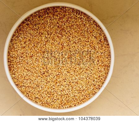 Creamish variety of sesame seeds kept in a bowl on a plain background