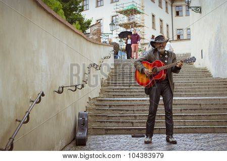 A street musician with a hat and with a guitar, Prague