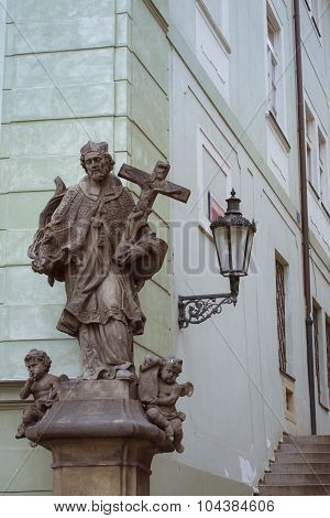 Stone statue of man with cross in district Mala Strana Prague's