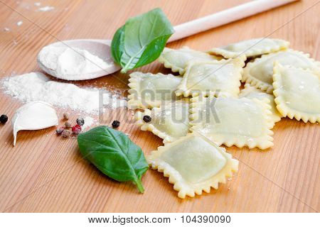 Raw Ravioli With Flour On Wooden Table