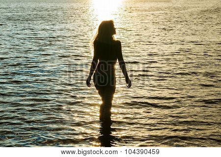 silhouette woman at sunset in water